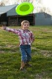Rolig pojke som kastar frisbeen Arkivbild