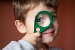 Rolig pojke som ser till och med förstoringsglaset med överraskning arkivbilder