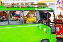 Rolig pojkeridning för liten unge på en karusellkarusell Arkivfoto