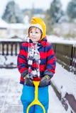 Rolig pys i färgrik kläder som är lycklig om snö, utomhus arkivbilder
