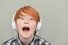 Rolig röd haired pojke med hörlurar Royaltyfri Bild
