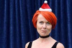 Rolig rödhårig mankvinna som bär en jultomtenhatt royaltyfria foton