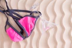 Rolig rosa bikiniöverkant och martini exponeringsglas på stranden royaltyfria foton