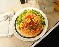 Rolig seende 'matframsida som göras av spagetti, tomatsås och en blandning av grönsaker arkivbild