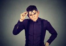 Rolig seende skeptisk vresig ung man i exponeringsglas arkivfoto