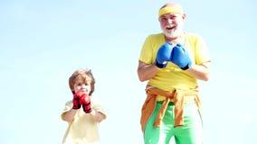 Rolig skäggig man - farfadern med barnpojkeanseende i boxning poserar Äldre man som slår den stansa påsen boxas f?r brunettflicka arkivfilmer