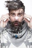 Rolig skäggig man i en bild för ` s för nytt år med snö och garneringar på hans skägg Festmåltid av jul royaltyfria foton
