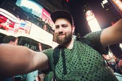 Rolig skäggig manfotvandrare som ler och tar selfiefotoet på Times Square i New York medan lopp över USA Fotografering för Bildbyråer