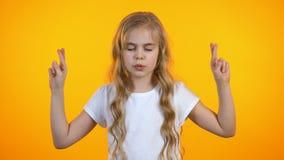 Rolig skolflicka som korsar fingrar och ber och att fråga för dröm- födelsedaggåva stock video