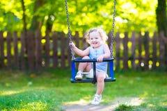 Rolig skratta svängande ritt för litet barnflicka på lekplats Royaltyfri Bild