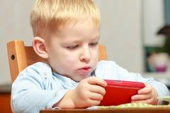 Rolig smutsig pojkebarnunge som tar fotoet med den inomhus röda mobiltelefonen Arkivbild