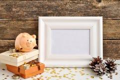 Rolig spargris med pengarsymbol av det nya året 2019 bredvid den vita fotoramen och att sörja kottar på lantlig träbakgrund arkivfoto