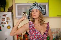 Rolig stående av hemmafrun i kök Arkivfoto