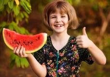 Rolig st?ende av den incredibly h?rliga lilla flickan som ?ter vattenmelon, sunt fruktmellanm?l royaltyfri bild