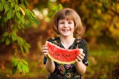 Rolig st?ende av den incredibly h?rliga lilla flickan som ?ter vattenmelon, sunt fruktmellanm?l arkivbilder