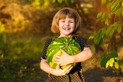 Rolig st?ende av den incredibly h?rliga lilla flickan som ?ter vattenmelon, sunt fruktmellanm?l royaltyfri fotografi