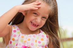 Rolig tandlös liten flicka utomhus Arkivfoto