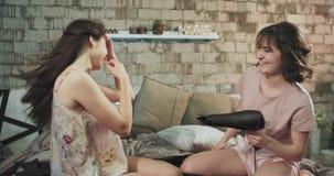 Rolig tid för damer för två vänner att sitta på bära för säng pyjamas och att använda en hårtork till nyare blickar arkivfilmer