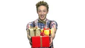 Rolig tonårig pojke som ger gåvaaskar lager videofilmer