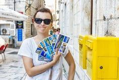 Rolig turist- kvinna med den near gula stolpeasken för postcarsd i Trogi Royaltyfri Bild
