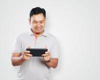 Rolig ung asiat Guy Playing Games på minnestavlan Royaltyfri Bild