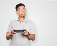 Rolig ung asiat Guy Playing Games på minnestavlan Arkivfoton
