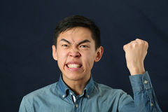 Rolig ung asiatisk man som skakar hans näve och uppåt ser Royaltyfri Bild