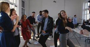 Rolig ung europeisk affärsmanchefdans samman med multietniska kontorskollegor som firar lagframgång arkivfilmer