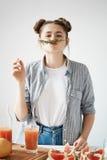 Rolig ung flicka med bullar som gör mustaschen med rosmarinfrunch som ser kameran som förbereder den sunda grapefruktdetoxen Fotografering för Bildbyråer