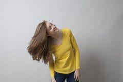 Rolig ung flicka som spelar med hennes långa bruna hår för hårskönhet Arkivfoto