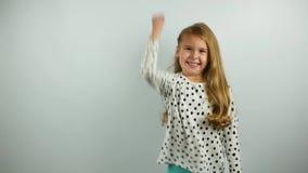 Rolig ung flicka som två gånger visar framgånggest på den vita bakgrunden långsam rörelse stock video
