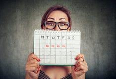 Rolig ung kvinna i exponeringsglas som döljer bak en periodkalender och ser kameran royaltyfri bild