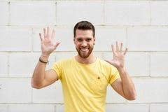 Rolig ung man på tegelstenväggen med öppet le för händer arkivbilder