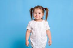 Rolig unge i den vita T-tröja på blå bakgrund Liten nätt flicka som isoleras på blå bakgrund Kopiera utrymme för text royaltyfria bilder