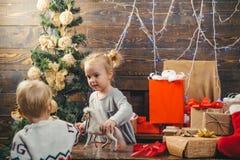Rolig unge som rymmer julg?van Inneh?ller genomskinliga objekt Det gulliga lilla barnet dekorerar julgranen inomhus ungar royaltyfri fotografi