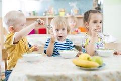 Rolig ungegrupp som äter i dagis fotografering för bildbyråer
