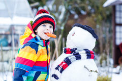Rolig ungepojke i färgrik kläder som gör en snögubbe, utomhus Royaltyfri Fotografi