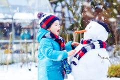 Rolig ungepojke i färgrik kläder som gör en snögubbe, utomhus Arkivbild
