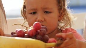 Rolig video av den lilla gulliga flickan som spelar med frukter på balkongen stock video