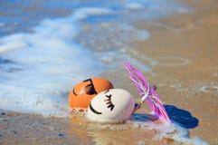 Roliga ägg för påsk under paraplyet på en strand arkivfoton