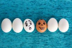Roliga ägg i rad, en är röda, andra förvånas Arkivbilder