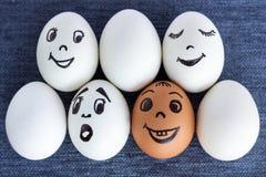 Roliga ägg med framsidor, en är röda, förvånade andra Arkivfoto