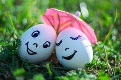 Roliga ägg som imiterar lyckliga par av att le vänner under umbrel Royaltyfria Bilder