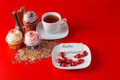Roliga barn frukosterar muffin på röd bakgrund för brigth Arkivfoto
