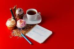 Roliga barn frukosterar muffin på röd bakgrund för brigth Arkivbild