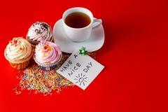 Roliga barn frukosterar muffin på röd bakgrund för brigth Royaltyfria Foton