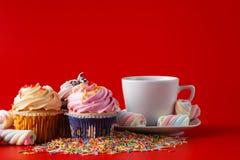 Roliga barn frukosterar muffin på röd bakgrund för brigth Royaltyfri Bild