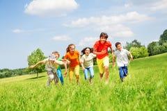 Roliga barn som kör i fältet Arkivfoton