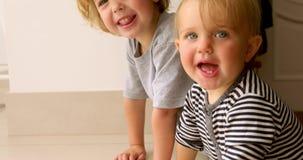Roliga barn som sitter på golv lager videofilmer