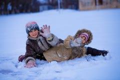 Roliga barn som spelar och skrattar på snöig vinter Arkivfoto